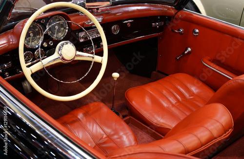 Photo sur Aluminium Vintage voitures Schwarzer Sportwagen mit roten Ledersitzen / Deutscher Oldtimer mit schicken Armaturen und Elfenbeinlenkrad