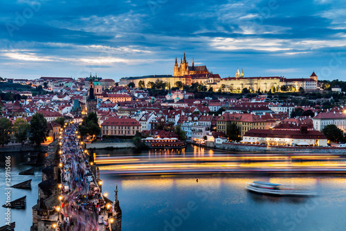 Fotobehang Praag View on Prague and its famous Charles bridge over Vltava river soon after sunset with boat lights trails