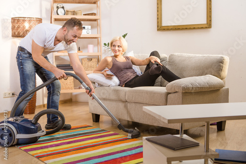 Happy Handsome Man Using Vacuum Cleaner For Cleaning House At Home. Blond  Wife Resting And Relaxing On Sofa Or Couch And Smiling To Him.