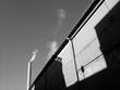 Licht und Schatten auf der Fassade einer alten Fabrik im Sonnenschein mit Schornstein eines Kraftwerk am Hafen von Münster in Westfalen im Münsterland, fotografiert in klassischem Schwarzweiß