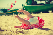 Small Child Fell Over On The Sand.