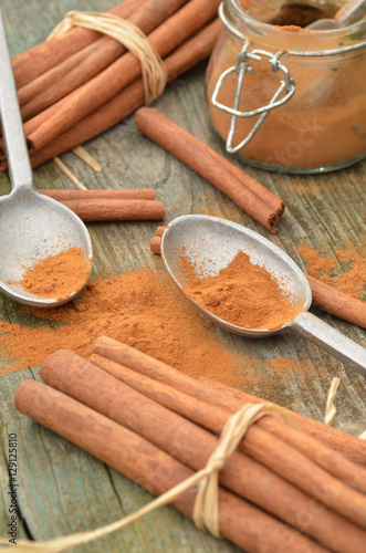 Canvas Prints Condiments cinnamon spice ground powder with cinnamon sticks and spoons