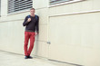 Man in red jeans in the city, a yellow wall