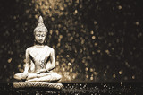 Buddha statue on a bright shiny background with bokeh. Photo in vintage style