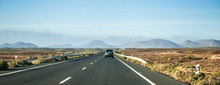 Car Driving Away To Mountains In Canary Island Desert