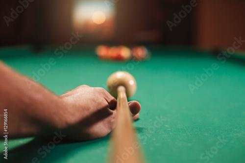 Photo Man preparing to break spheres in billiards.