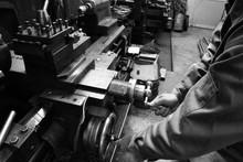 Craftsman Using The Obsolete Lathe. Black-and-white Photo.