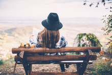 Hipster Woman Sitting On Bench And Looking For Direction On Viewpoint