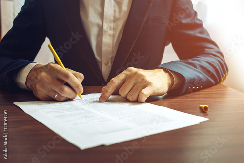 Fotografía  Man businessman signs documents with a pen