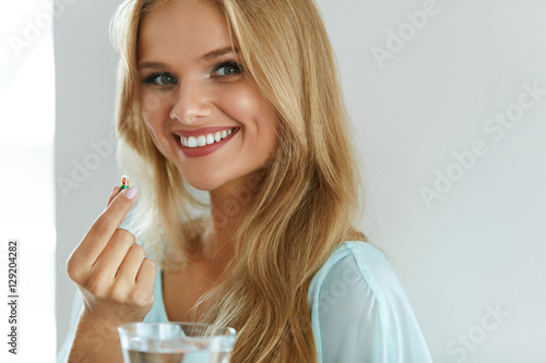 Obraz Beautiful Smiling Woman Taking Vitamin Pill. Dietary Supplement - fototapety do salonu