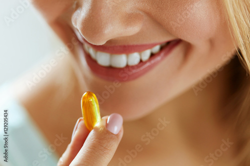 Fototapeta Close Up Of Beautiful Woman Taking Fish Oil Capsule In Mouth obraz