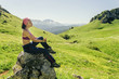 Young woman sitting on a rock and enjoying mountain valley view