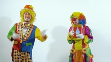 Two Funny Circus Clowns Playing With A Red Glossy Box, Throwing It To The Air