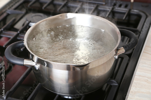 Valokuva  Water boiling into saucepan on the gas stove