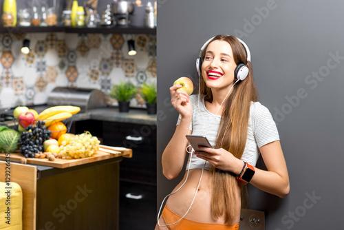 Plakat Stylu życia portret młoda sport kobieta słucha muzyka z telefonem i hełmofonami w nowożytnym kuchennym wnętrzu folującym z owoc i warzywo