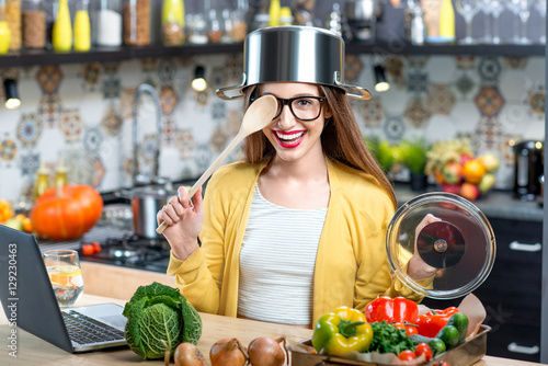 Photo  Funny portrait of a young and happy woman with cooking pan and spoon in the kitc