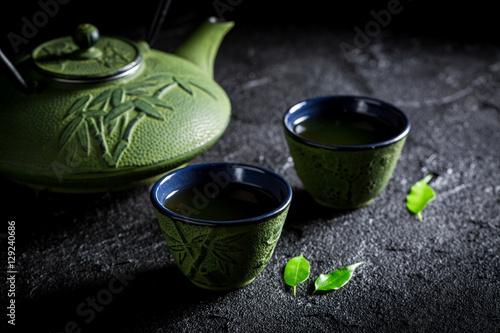 zielona-herbata-w-zielonym-czajniczku-i-filizankach-na-czarnej-skale