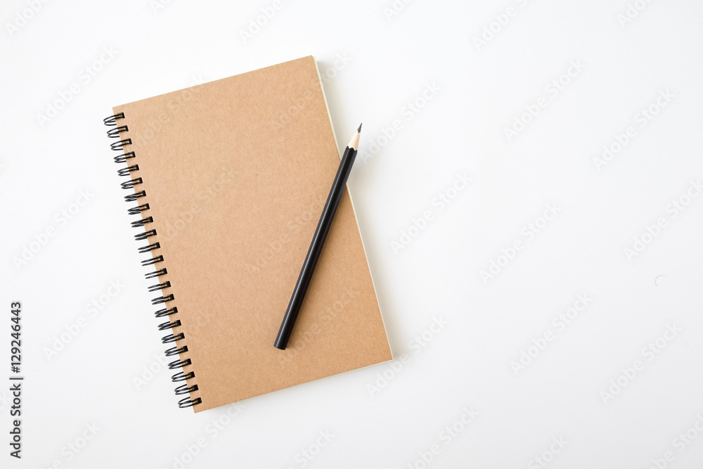 Fototapeta Top view of closed spiral blank craft paper cover notebook with pencil on white desk background