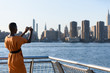 African business woman taking picture on the phone outdoor, New York, Manhattan, skyline view