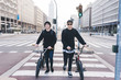 Two young guys walking holding bmx