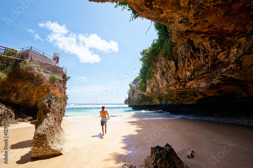Foto op Aluminium Bali Hobby and vacation. Young man with surfboard on beautiful beach with high rocks. Uluwatu spot, Bali island, Indonesia.