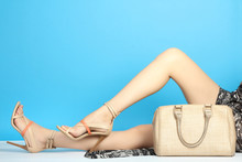 Women's Sexy Legs In Sandals High-heeled Shoes With Beige Bag On A Blue Background.