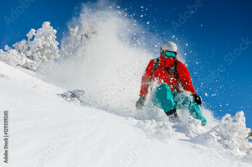 Skier skiing downhill in high mountains Fototapeta