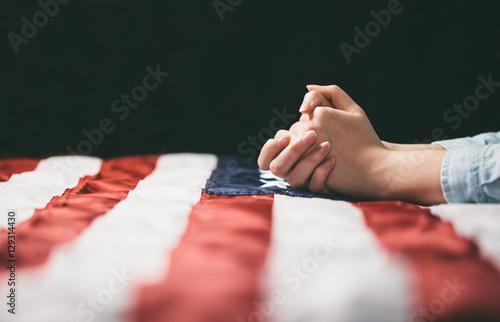 Fotografía  Hands praying over USA flag