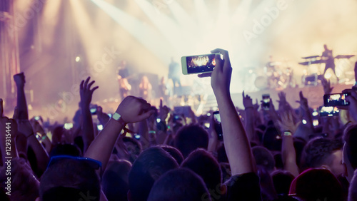 Fototapeta Fan taking photo of concert obraz