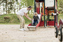 Happy Father Looking At Son Playing On Slide At Playground
