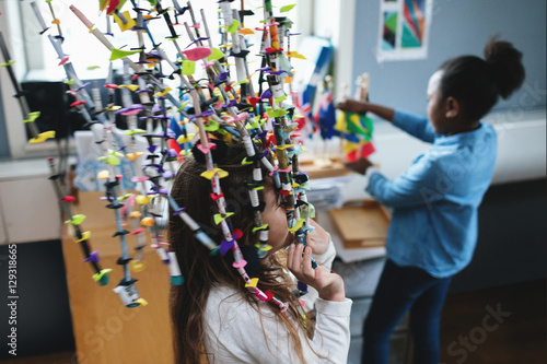 Girl playing with decoration while friend looking at flags in classroom
