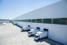 Facade Of An Industrial Building And Warehouse With Freight Cars In Length