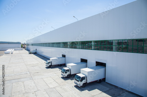 Poster Industrial geb. facade of an industrial building and warehouse with freight cars in length
