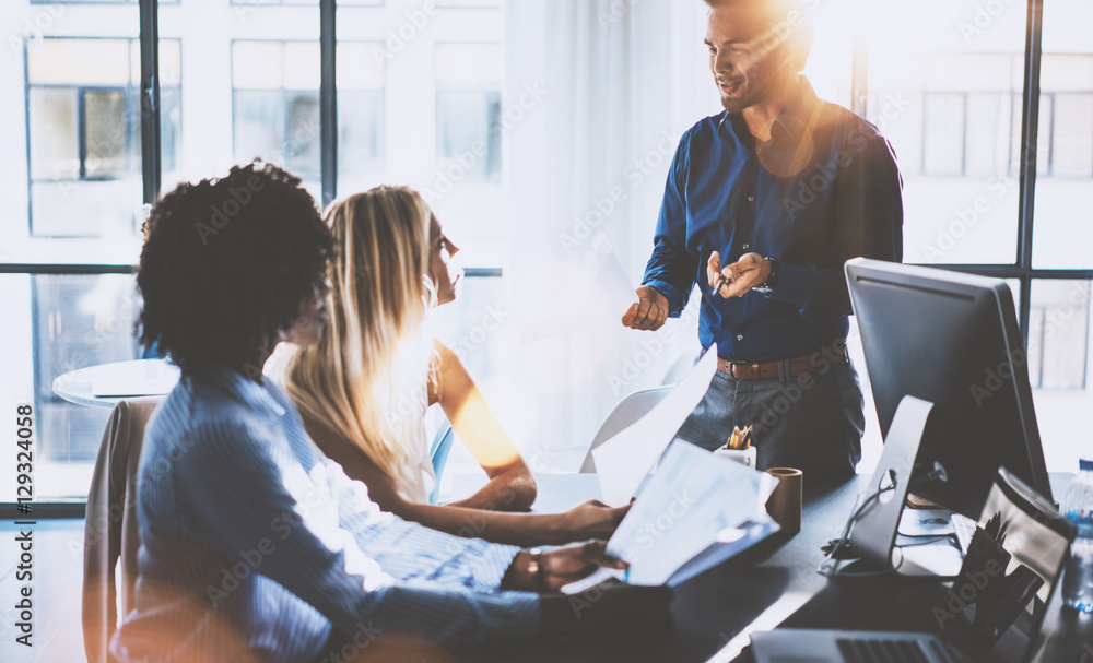Fototapeta Young team of coworkers making great meeting discussion in modern coworking office.Hispanic businessman talking with two beautiful womans.Teamwork process.Horizontal,blurred background,flares effect.