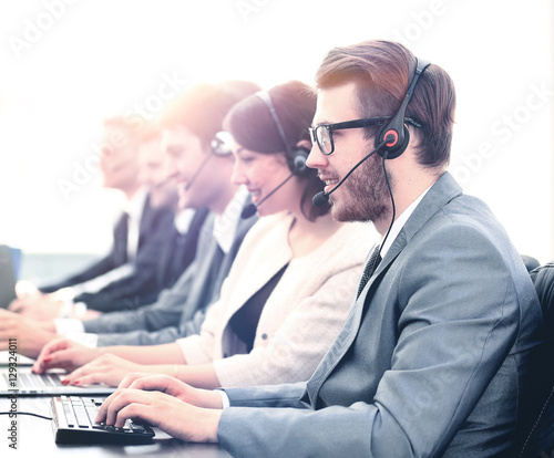 Fototapeta Attractive young man working in a call center with his colleagues obraz