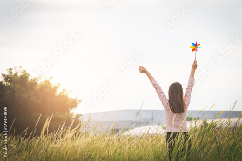 Fotografie, Tablou  Silhouette of Beautiful girl holding wind toy or wind turbine or pinwheel and wool hat at meadow on winter season in morning