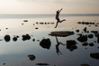 silhouette of a young girl soaring in a jump on the beach at sunrise with reflection in water