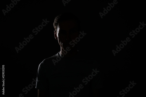 Fototapeta Young man in t-shirt on dark background. obraz