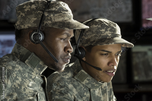 Photo  2 military drone operators in front of a computer, close up