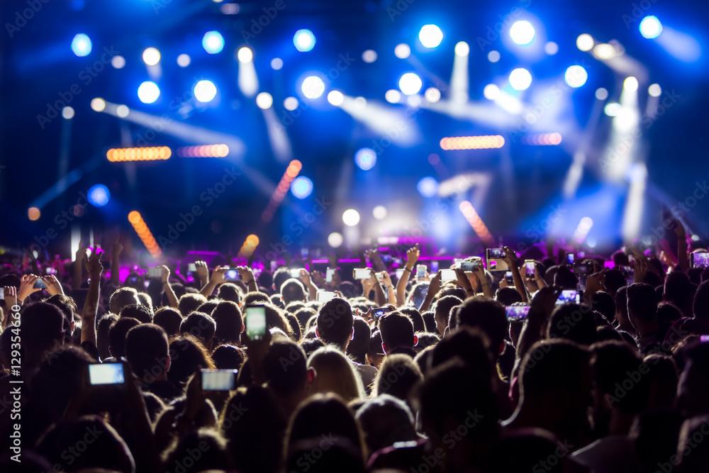 Fototapeta Hand with a smartphone records live music festiva