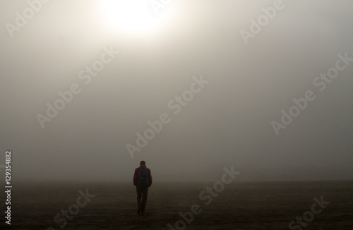 Fotografía  hiker walks alone in a sea of sand in the fog