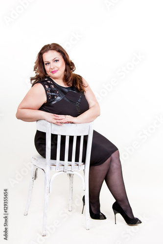 8fc3fe4e61f Beautiful young plus size woman in black dress sitting on a chair on a  white background. Chubby woman is sitting on a white chair in a dress.  pantyhose and ...