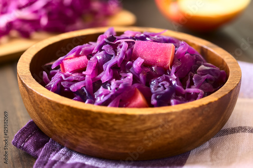 Canvas-taulu Braised red cabbage with apple in wooden bowl, with ingredients in the back, pho