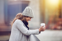 Beautiful Happy Young Adult Woman Drinking Coffee Near New York City Skyline Wearing Winter Clothes And Smiling. Beautiful Woman Holding Coffee Cup Outdoors In The City.