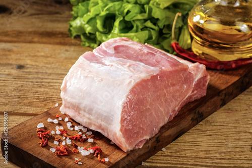 Photo  Raw pork loin with salt and herbs.