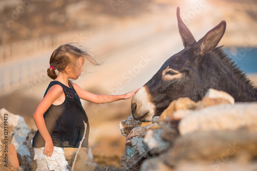 Poster de jardin Ane Little girl with donkey on the island of Mykonos