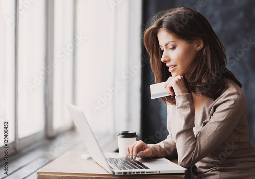 Fotografía  Young woman holding credit card and using laptop computer