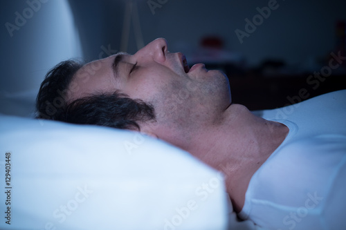 Photo Man is sleeping in his bed