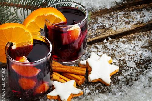 Glühwein mit Orange und Zimtsterne auf Holz