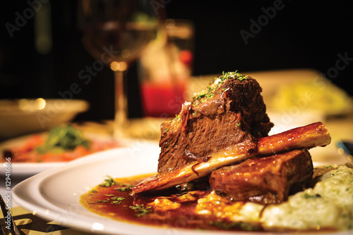 Close up of braised beef short rib on dinner table. Selective focus.